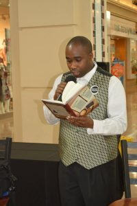 Troy Legette at a book reading in a mall, hold the book open in his hand with a microphone.