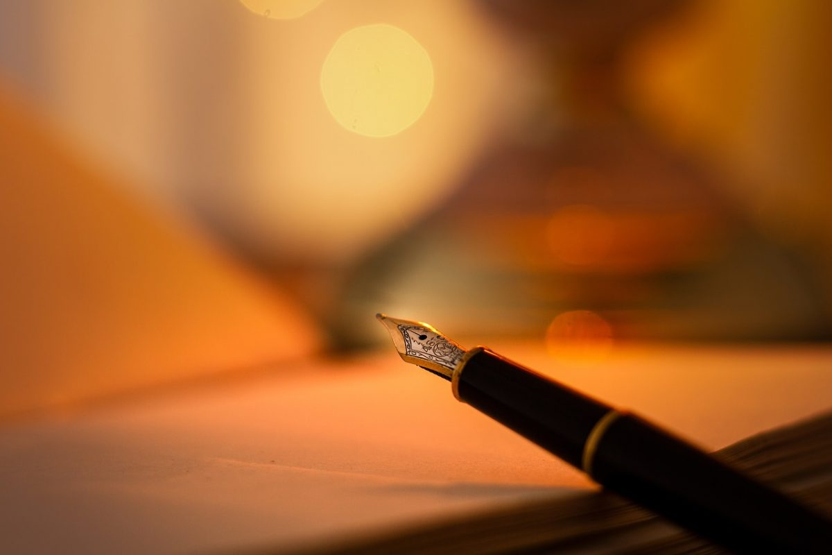 A picture of an ink pen next to a notebook. Writing poetry for beginners.